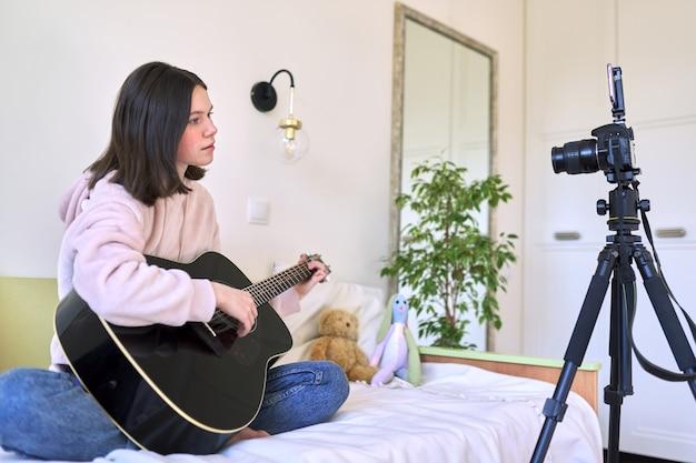 Ragazza teenager che si siede a casa a letto con una chitarra acustica, ragazza che impara a suonare la chitarra in linea. tecnologia, social network, arte, hobby, concetto di adolescenti