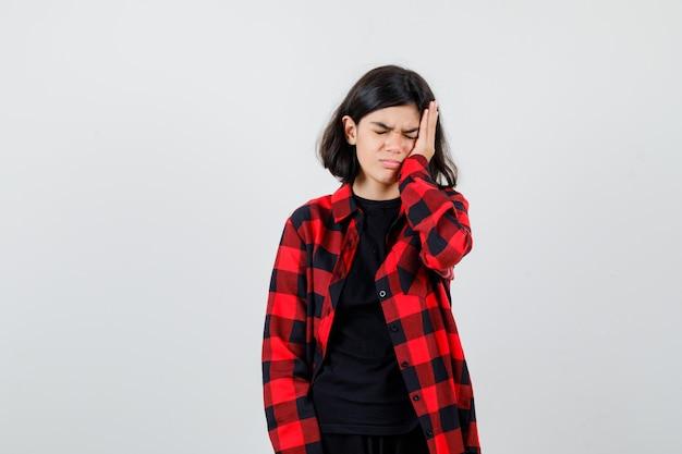 Ragazza teenager che soffre di mal di testa in maglietta, camicia a scacchi e sembra dolorosa. vista frontale.