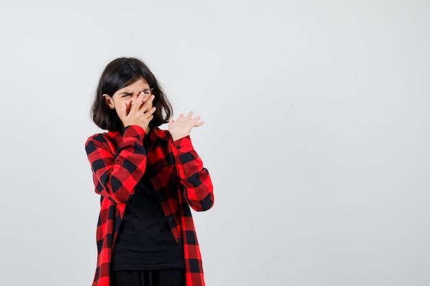 Ragazza teenager in t-shirt, camicia a scacchi che tiene la mano sulla bocca, alzando il palmo e guardando spaventata, vista frontale.