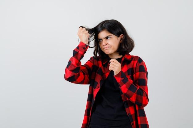 Ragazza teenager in t-shirt, camicia a scacchi che tiene ciocche di capelli e sembra delusa, vista frontale.