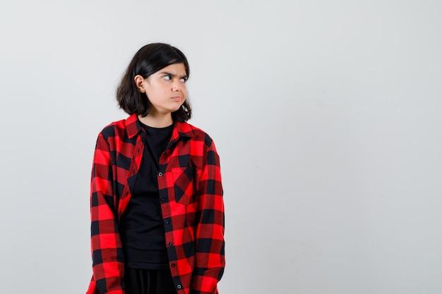 Ragazza teenager in t-shirt, camicia a scacchi che guarda da parte e sembra dispettosa, vista frontale.