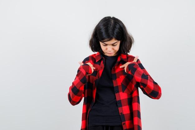 Ragazza teenager in t-shirt, camicia a scacchi che punta a se stessa e sembra indecisa, vista frontale.