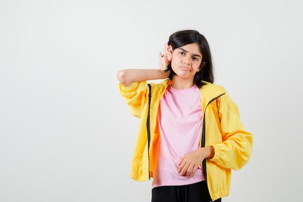 Ragazza teenager in t-shirt, giacca che tiene la mano dietro l'orecchio e sembra sconvolta, vista frontale.