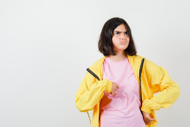 Ragazza teenager in maglietta, giacca che indica se stessa e sembra confusa, vista frontale.