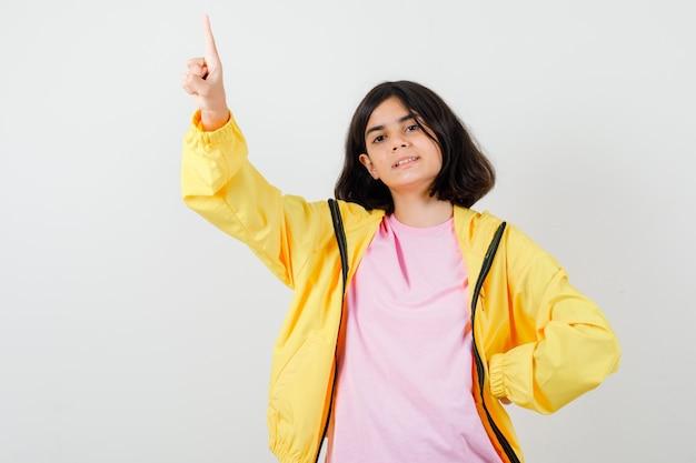 Ragazza teenager in t-shirt, giacca rivolta verso l'alto e dall'aspetto fiducioso, vista frontale.