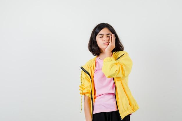 Ragazza teenager in maglietta, giacca che soffre di mal di denti e sembra dolorosa, vista frontale.
