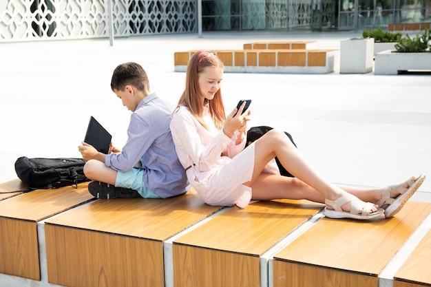 Gli scolari di una ragazza adolescente e di un ragazzo adolescente si siedono con gli zaini della scuola su una panca di legno tra pareti di cemento, schiena contro schiena, usano dispositivi mobili