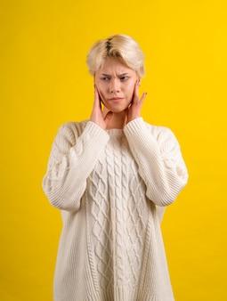 Ragazza teenager con taglio di capelli bianco corto che indossa un maglione lavorato a maglia bianco ha mal di denti
