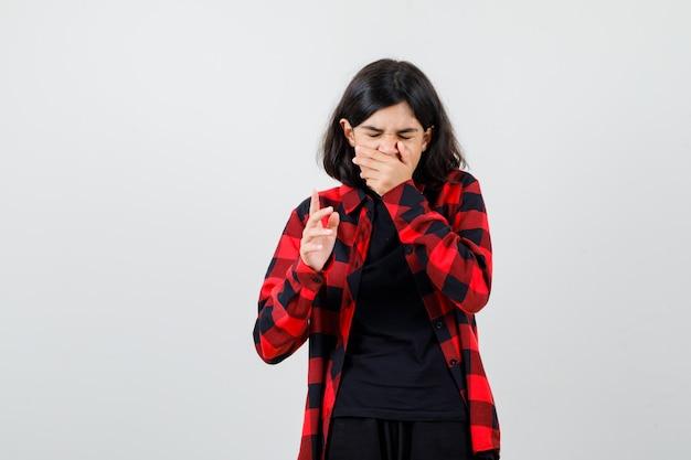 Ragazza teenager che sbadiglia mentre tiene la mano sulla bocca in maglietta, camicia a scacchi e sembra assonnata. vista frontale.