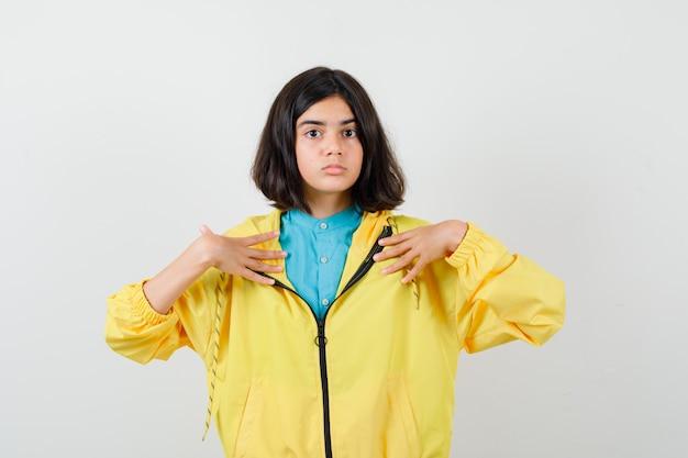 Ragazza teenager in giacca gialla che indica se stessa e sembra perplessa, vista frontale.