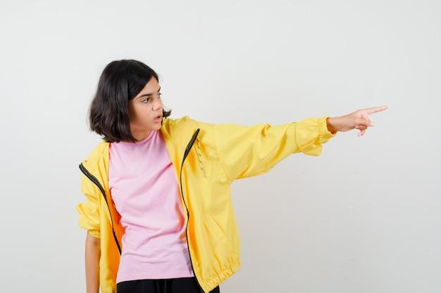 Ragazza teenager in tuta gialla, t-shirt che punta di lato e sembra sorpresa, vista frontale.