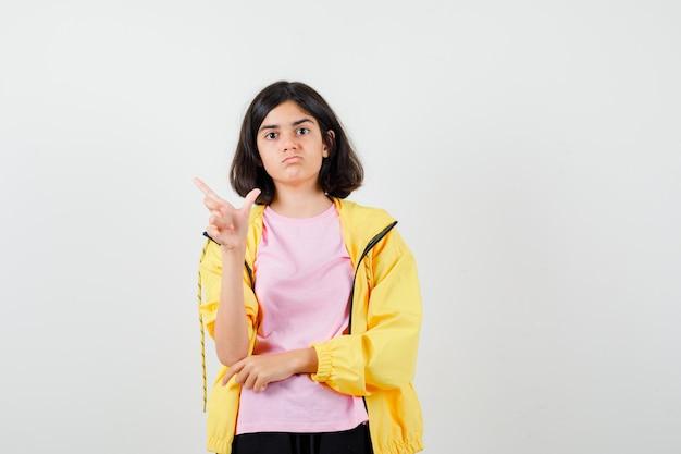 Ragazza teenager in tuta gialla, t-shirt che mostra il gesto del perdente e sembra malinconica, vista frontale.