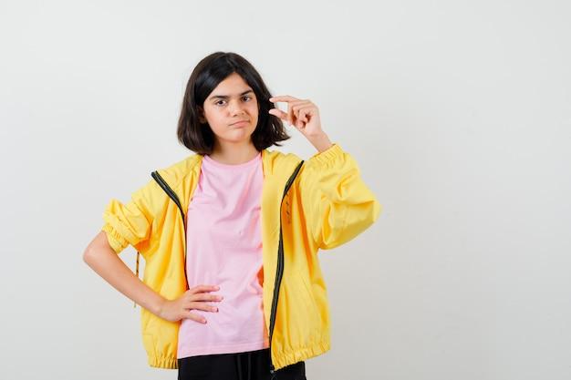 Ragazza teenager in tuta gialla, t-shirt che mostra taglia piccola, tenendo la mano sul punto vita e guardando premurosa, vista frontale.