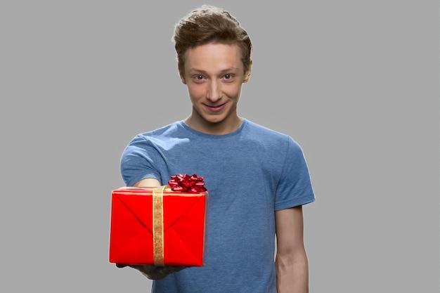 Ragazzo teenager che dà confezione regalo alla telecamera. bel ragazzo adolescente che offre casella presente su sfondo grigio.