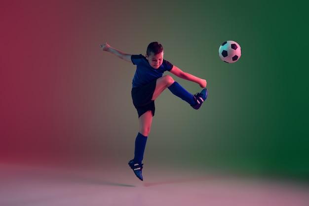Giocatore di calcio o di calcio maschio adolescente, ragazzo su gradiente in luce al neon