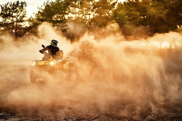 Adolescente che guida l'atv nelle dune di sabbia che fa un giro nella sabbia