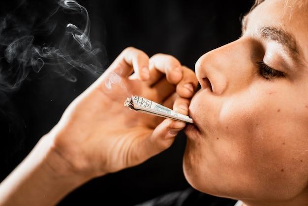 Teen fumare una sigaretta o droghe è un dollaro arrotolato, il concetto di dipendenza da adolescenti e spendere soldi per le sigarette, orrore