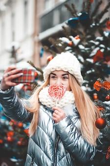 Teenager con la lecca-lecca che fa selfie con l'albero di natale