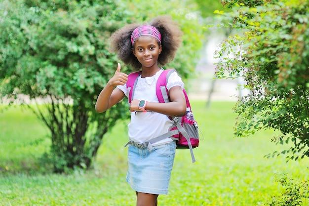 Adolescente afroamericana con uno zaino da scuola e uno smartwatch in mano contro lo sfondo...