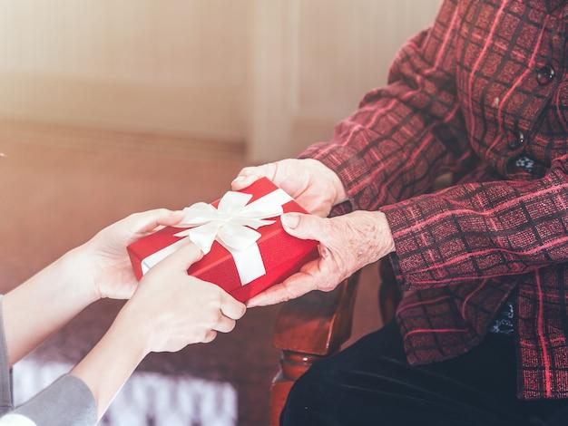 La ragazza adolescente dell'asia sta dando alla nonna che si siede sulla sedia un bellissimo giftbox per l'idea di festa di compleanno di giorno di madri a casa con sfondo scuro, close up, copia spazio, vista ritagliata