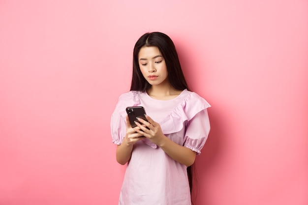 Adolescente ragazza asiatica in chat sul telefono cellulare, guarda lo schermo dello smartphone con la faccia seria, in piedi su sfondo rosa.