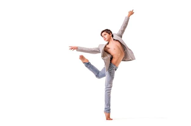 Un ballerino adolescente posa a piedi nudi, isolato su uno spazio bianco.