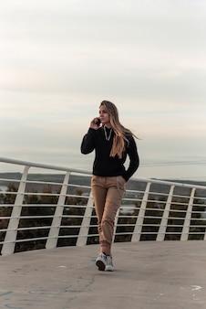 Adolescente bionda che fa una chiamata sul suo telefono cellulare mentre si cammina su un ponte urbano bianco.