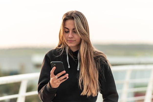 Adolescente bionda usando il suo telefono cellulare. camminando su un ponte urbano bianco.