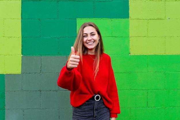 Donna bionda adolescente con un maglione rosso che fa il simbolo giusto.