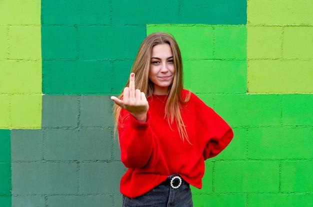 Donna bionda adolescente con un maglione rosso. mostrando il suo dito medio