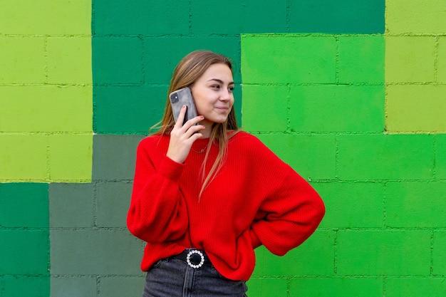 Donna bionda adolescente con un maglione rosso che parla con il suo telefono cellulare.