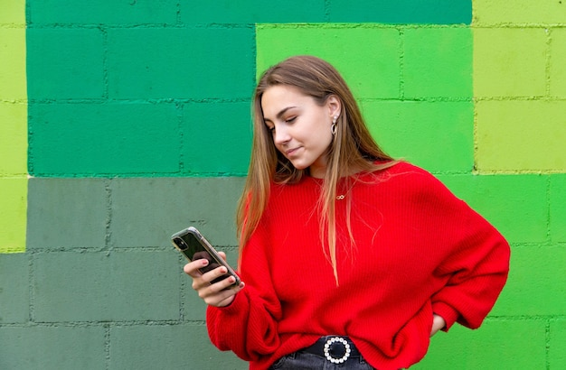 Donna bionda adolescente con un maglione rosso utilizzando il suo telefono cellulare.