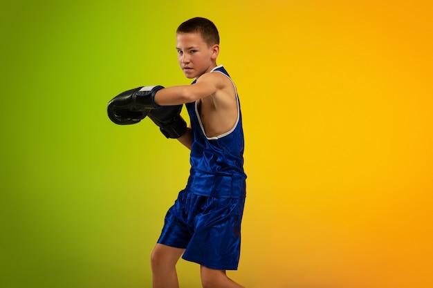 Pugile adolescente contro lo sfondo dello studio al neon sfumato in movimento di kicking boxing
