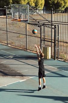 Ragazzo adolescente giocatore di basket che si allena da solo al campo sportivo lanciando la palla