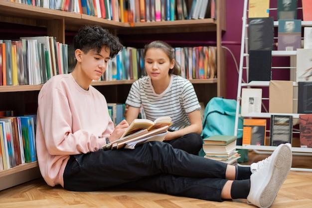 Ragazzo adolescente in abbigliamento casual che tiene il libro aperto e che indica alla pagina mentre mostra il passaggio del compagno di classe per imparare a memoria