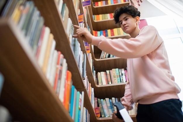 Ragazzo adolescente in abbigliamento casual che prende il libro dallo scaffale nella biblioteca del college mentre ne sceglie uno per una lettura approfondita a casa