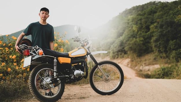 Un adolescente e una classica moto da enduro su una strada rocciosa.