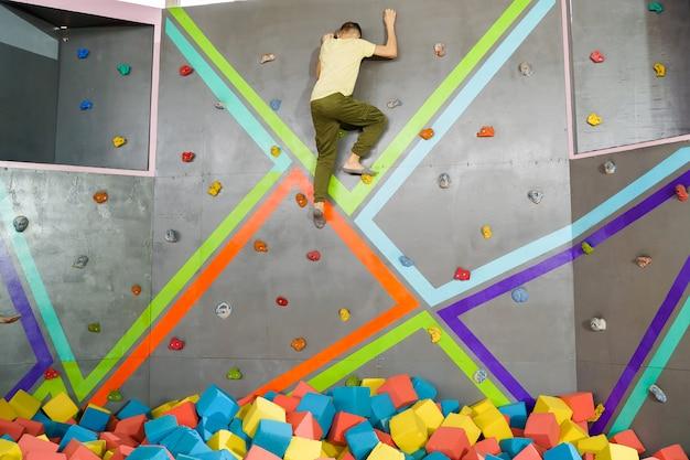 Adolescente sulla parete rampicante nel centro del trampolino.