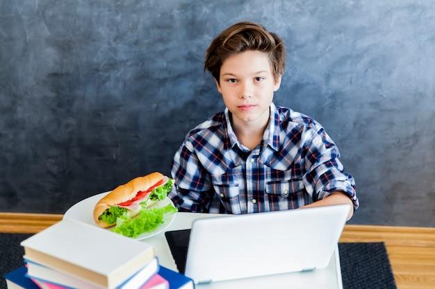 L'adolescente mangia un panino e naviga sul web