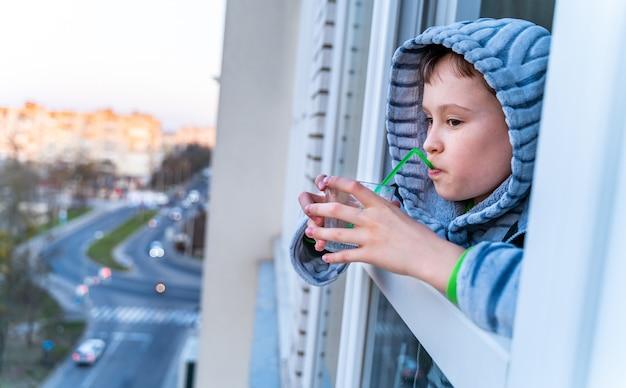 Ragazzo adolescente che guarda fuori dalla finestra di casa annoiato