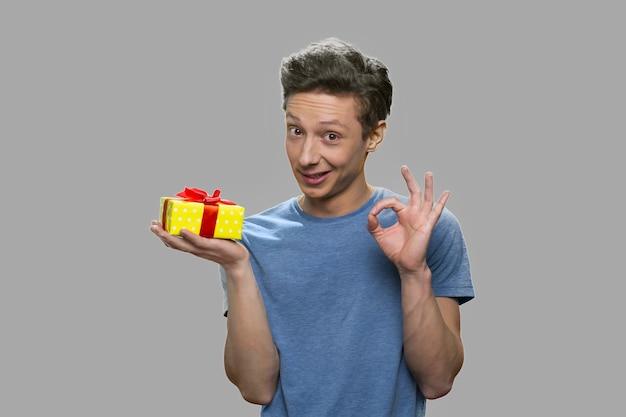 Ragazzo adolescente che mostra confezione regalo e gesto ok. bel ragazzo adolescente tenendo presente la casella su sfondo grigio.