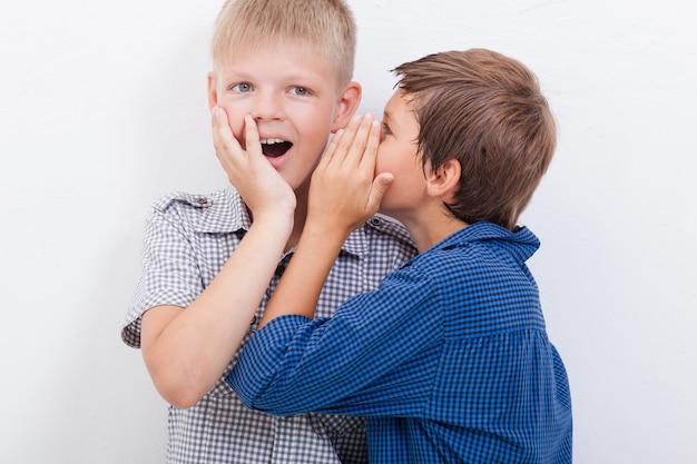 Ragazzo adolescente sussurra all'orecchio un segreto per l'amicizia su sfondo bianco
