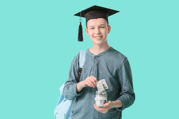 Ragazzo adolescente con risparmi per l'istruzione sulla superficie del colore