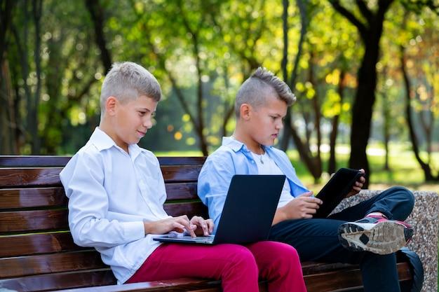 Adolescenti sul banco di parco facendo uso del computer portatile e della compressa di digital