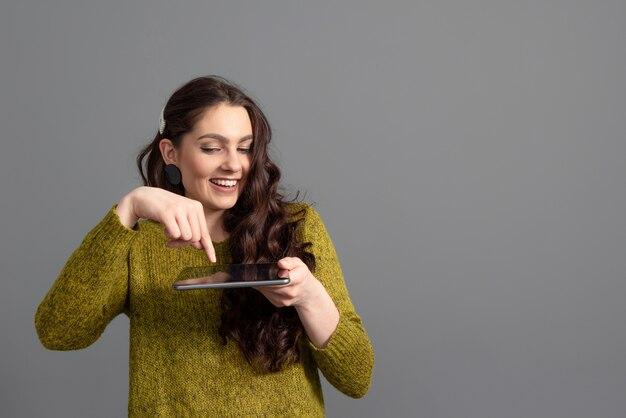 Femmina adolescente con lunghi capelli ondulati divertendosi con una tavoletta, isolata su una superficie grigia