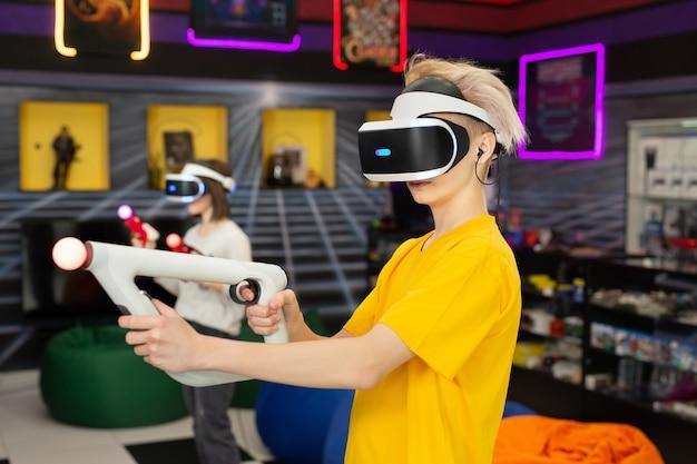Amici adolescenti, un ragazzo e una ragazza, con un auricolare per realtà virtuale in occhiali e controller di movimento della mano nel club di gioco.