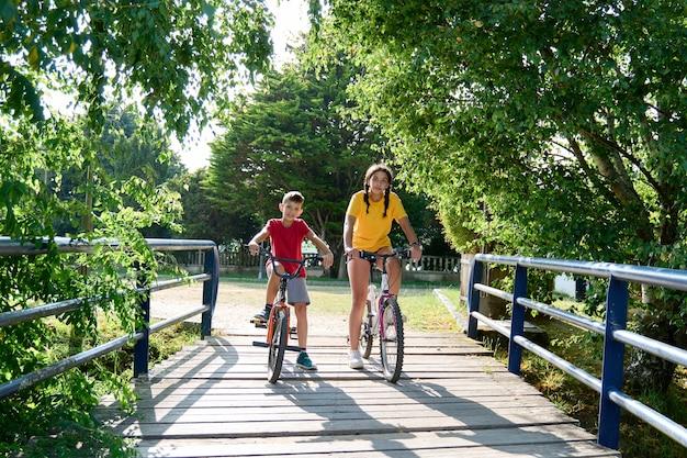 Una ragazza adolescente e un bambino di 8 anni sulle loro biciclette, concetto di relazione tra fratelli