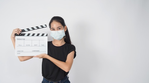 L'adolescente o la giovane donna asiatica indossano la maschera per il viso e la mano che tiene il ciak o l'uso dell'ardesia del film nella produzione di video, film, industria cinematografica su sfondo bianco.