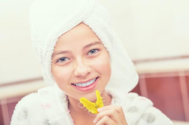 Ragazza adolescente in bagno con bretelle di fermo dentale. igiene dentale mattutina e serale.