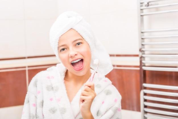 Adolescente in bagno con spazzolino da denti. igiene dentale mattutina e serale.